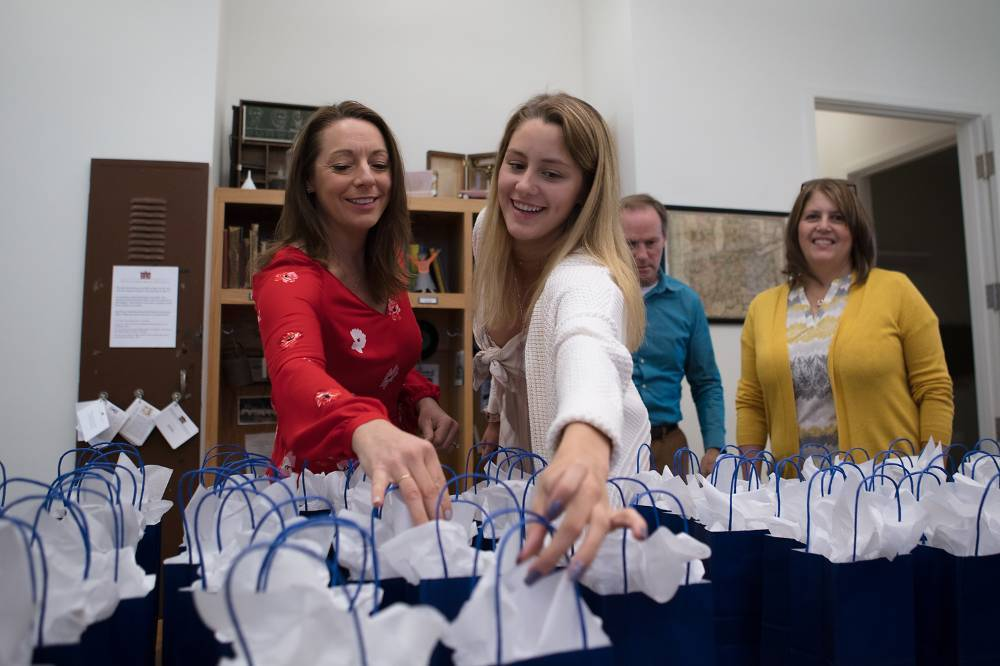 Two women smile while receiving a gift bag